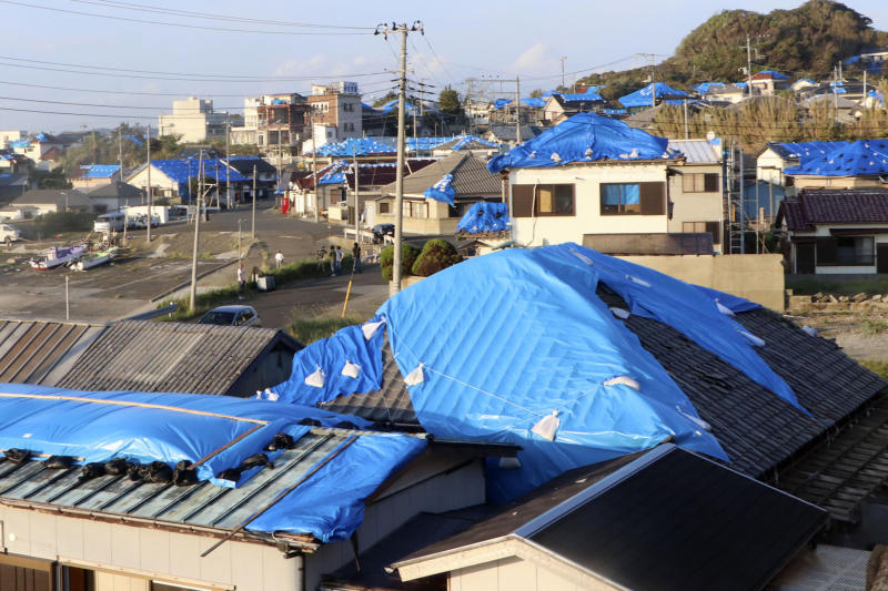 This Oct. 8, 2019, photo shows the sheet-covered roofs of the houses damaged by typhoon Faxai in Tateyama, near Tokyo.  Japan's weather agency is warning a powerful typhoon may bring torrential rains to central Japan over the weekend. (Kyodo News via AP)