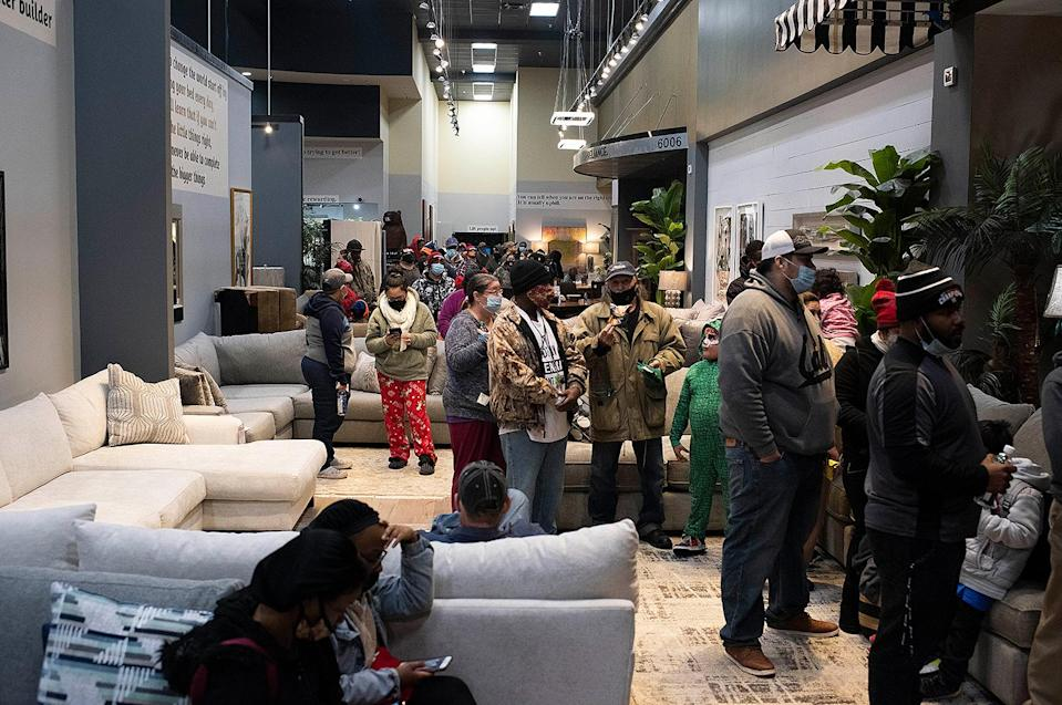 <p>People wait in line for food at Gallery Furniture in Houston, Texas, on Feb. 17. The store opened in two locations as warming centers. </p>
