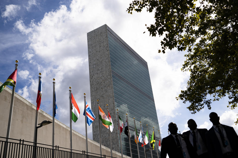 Members of a delegation's entourage wait outside a security checkpoint on the sidewalk in front of the United Nations headquarters, Tuesday, Sept. 21, 2021, during the 76th Session of the U.N. General Assembly in New York. (AP Photo/John Minchillo, Pool)