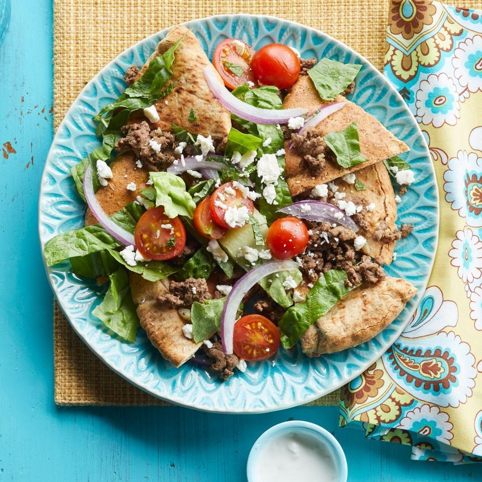 <p>Swap tortilla chips for pita chips in this healthy Mediterranean nacho recipe. For a party, create one large platter--just be sure to serve with plates!</p>
