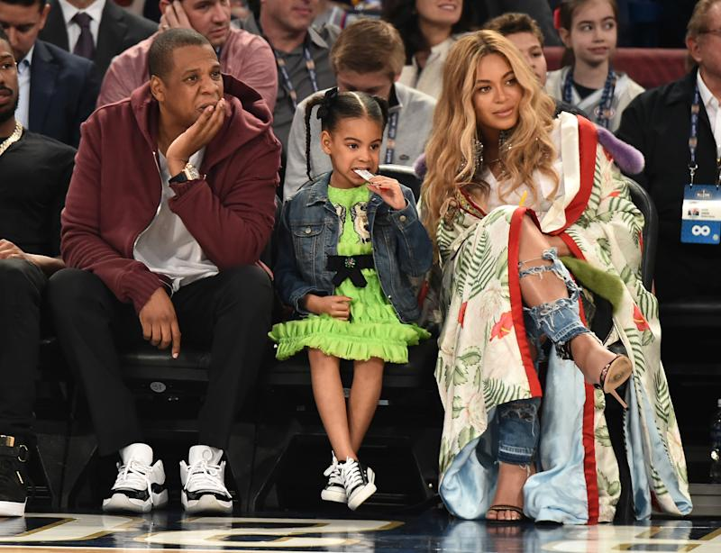 While Jay Z and Blue Ivy wore coordinating sneakers, Beyoncé Knowles stood out wearing a pair of strappy sandals and some sort of unexplainable poncho at the 66th NBA All-Star Game in New Orleans, Louisiana.
