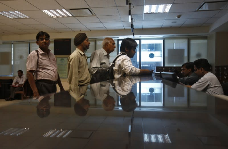 FILE PHOTO: People line to submit their papers inside the Income Tax office in New Delhi