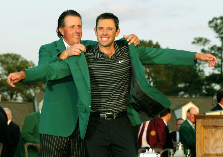 If the coat fits: The 2010 champion Phil Mickelson puts the green jacket on Charl Schwartzel after he won the 2011 Masters