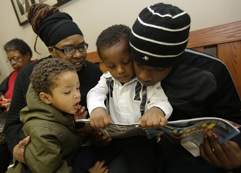 Evette Banks looks at a book with her adopted sons Braylin Banks, 2, center, Cameron Cole, 2, left, and Amir Freeman, right, Friday, Nov. 22, 2013, prior to adoption proceedings for Braylin in Cincinnati. (AP Photo/Al Behrman)