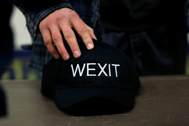 A supporter holds his Wexit hat while attending a rally in Calgary on Nov. 16, 2019.