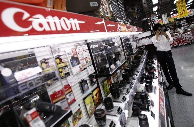 Man tries a Canon digital camera at an electronics retail store in Tokyo