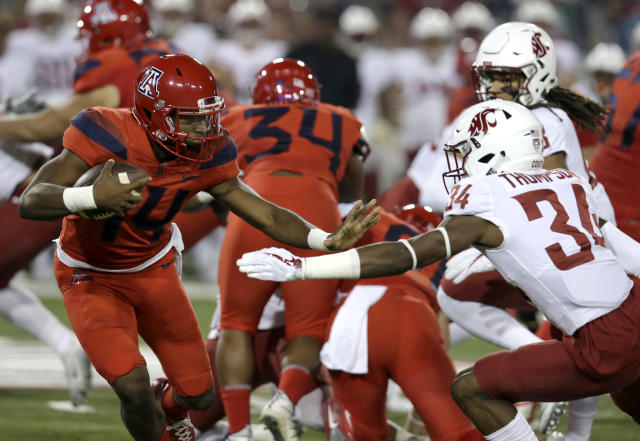Arizona quarterback Khalil Tate (14) stiff-arms Washington State safety Jalen Thompson (34) in the first half during an NCAA college football game, Saturday, Oct. 28, 2017, in Tucson, Ariz. (AP Photo/Rick Scuteri)