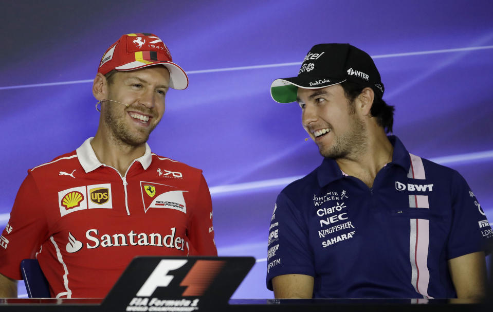 Ferrari driver Sebastian Vettel, left, of Germany smiles during a press conference with Force India driver Sergio Perez, of Mexico, ahead of Sunday's Formula One Italian Grand Prix, at the Monza racetrack, Italy, Thursday, Aug. 31, 2017. (AP Photo/Antonio Calanni)