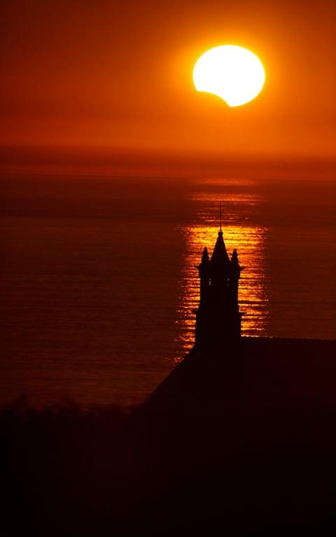 The Saint-They Chapel is seen in silhouette at sunset during a partial solar eclipse as the moon passes in front of the sun seen at the Pointe du Van - Credit: Reuters