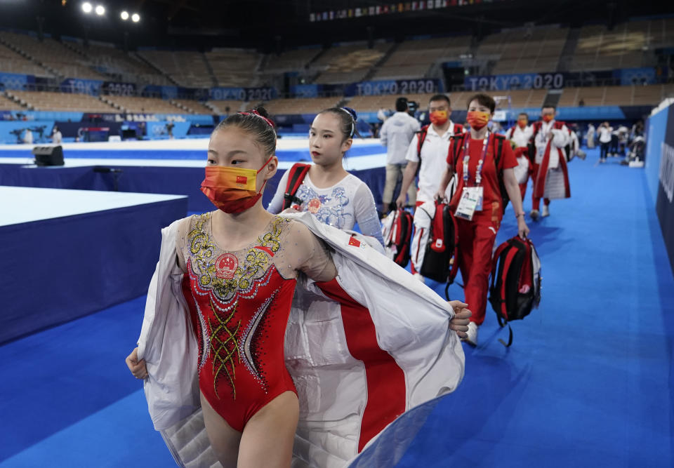 FILE - In this July 25, 2021, file photo, members of team China walk to the next apparatus during the women's artistic gymnastic qualifications at the 2020 Summer Olympics in Tokyo. Tokyo Olympians are exercising extraordinary discipline against the coronavirus. They are sealed off in a sanitary bubble that has made competition possible but is also squeezing a lot of fun from their Olympic experience. (AP Photo/Ashley Landis, File)