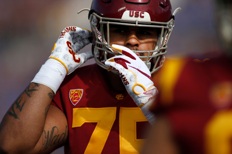 PASADENA, CALIFORNIA - NOVEMBER 17: Guard Alijah Vera-Tucker #75 of the USC Trojans adjusts his helmet.