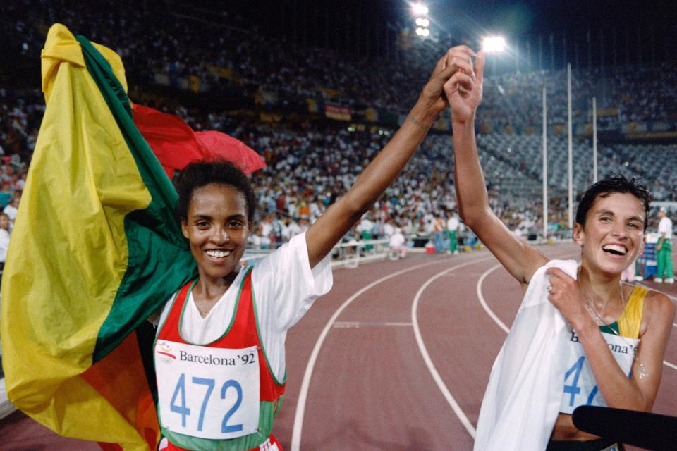 Ethiopia's Derartu Tulu (L) and Elana Meyer of South Africa join hands in a victory lap after the women's 10,000m final at the athletics event during the Barcelona 1992 Olympic Games on August 7, 1992 in Barcelona.  Tulu won the Olympic gold medal and Meyer took the silver. / AFP PHOTO / Pascal PAVANI        (Photo credit should read PASCAL PAVANI/AFP via Getty Images)