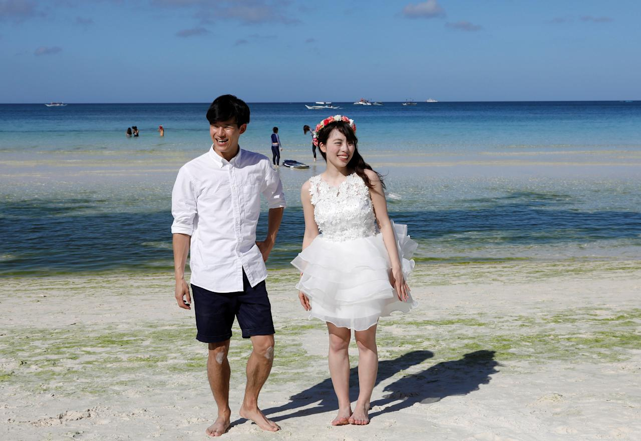 Newly-wed tourists stroll along the beach, two days before the temporary closure of the holiday island Boracay in Philippines April 24, 2018.  REUTERS/Erik De Castro