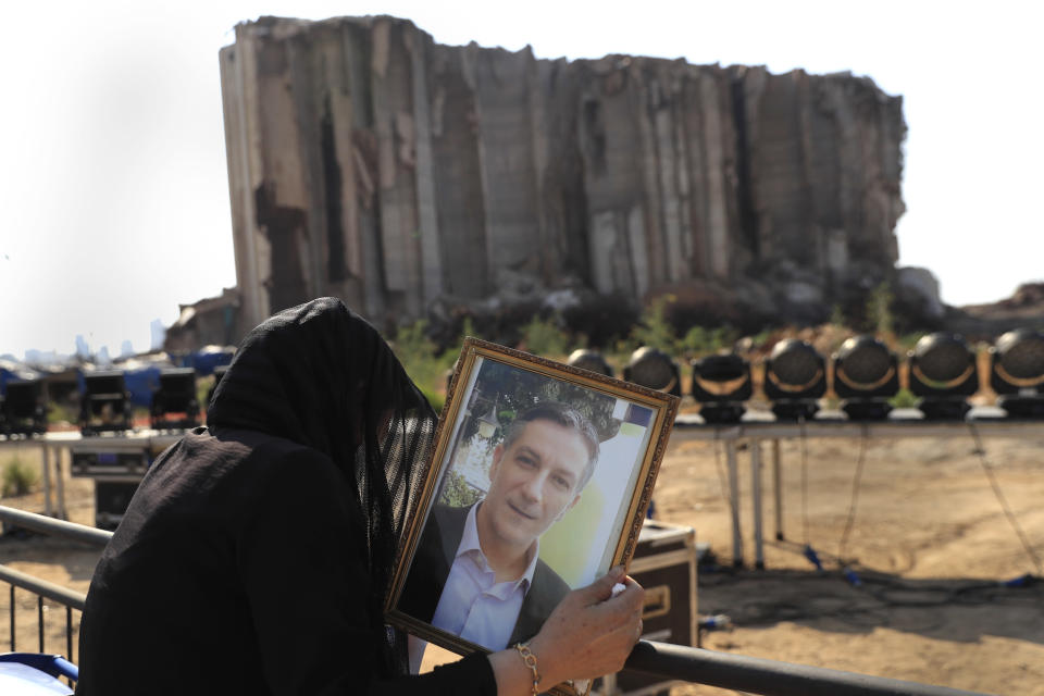 A relative of a victim who was killed in the massive blast last year at the Beirut port reacts and holds his portrait as she attends a mass held to commemorate the first year anniversary, at the Beirut port, Lebanon, Wednesday, Aug. 4, 2021. (AP Photo/Hussein Malla)