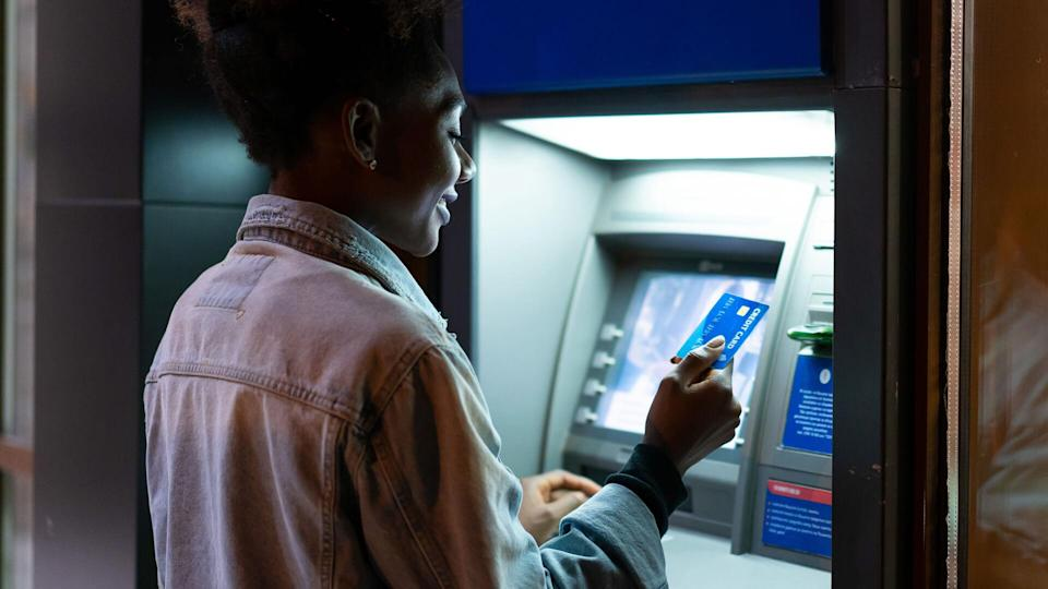 Afro American woman withdrawing money at the ATM.