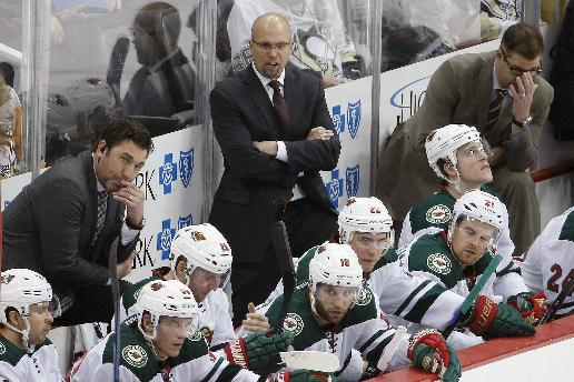 Minnesota Wild coach Mike Yeo, center, is flanked by assistants Andrew Brunette, left, and Darryl Sydor, right, behind the bench during the third period of an NHL hockey game against the Pittsburgh Penguins in Pittsburgh on Tuesday, Jan. 13, 2015. The Penguins won 7-2