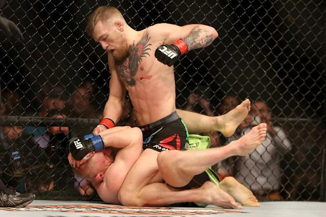 Conor McGregor, of Ireland,, top, lands punches against Dennis Siver, of Germany, during their featherweight fight at UFC Fight Night, Sunday, Jan. 18, 2015 in Boston. McGregor won via 2nd round TKO. (AP Photo/Gregory Payan)
