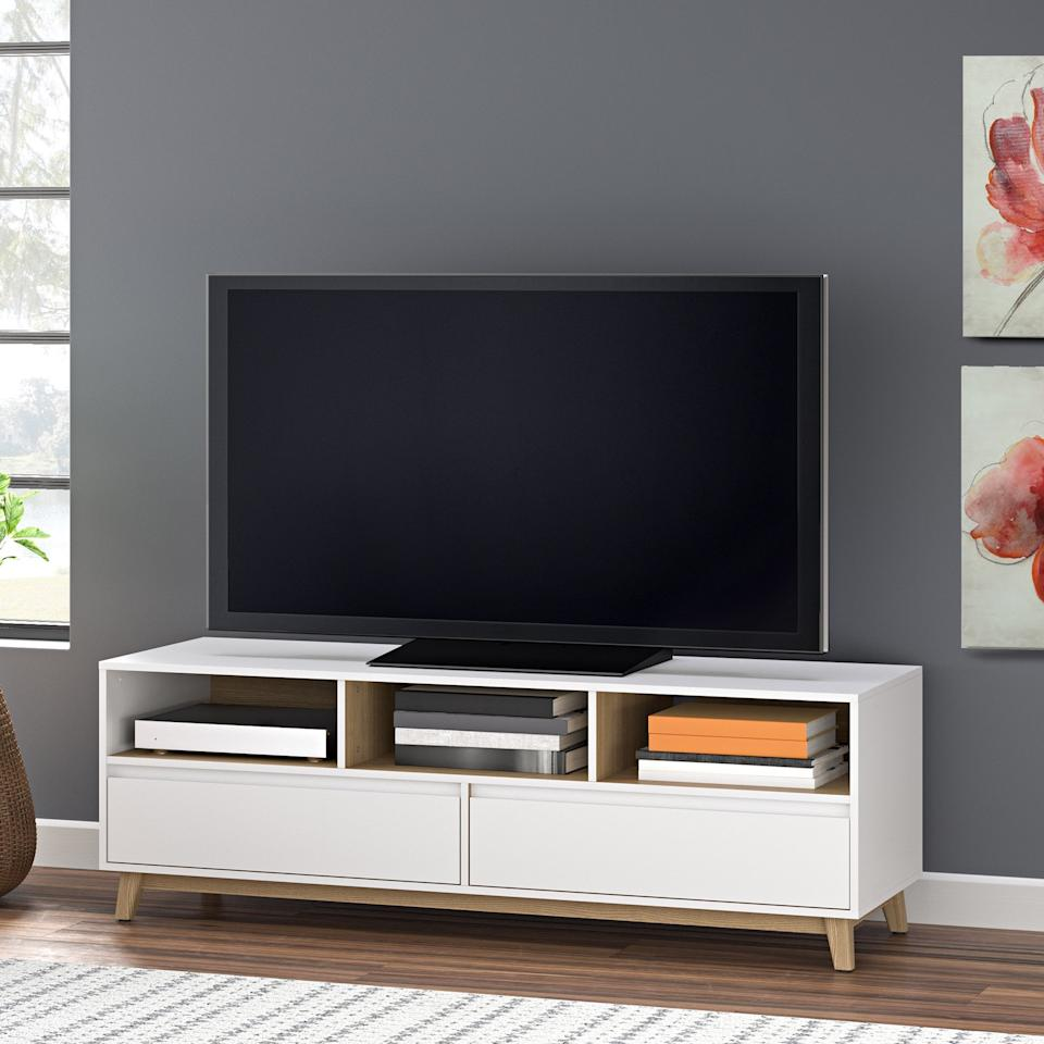 "<p>The wood base adds some dimension to this <a href=""https://www.popsugar.com/buy/Mainstays%20Mid-Century%20TV%20Stand-426894?p_name=Mainstays%20Mid-Century%20TV%20Stand&retailer=walmart.com&price=97&evar1=casa%3Aus&evar9=46366853&evar98=https%3A%2F%2Fwww.popsugar.com%2Fhome%2Fphoto-gallery%2F46366853%2Fimage%2F46367005%2FMainstays-Mid-Century-TV-Stand&list1=shopping%2Cfurniture%2Cwalmart%2Csmall%20space%20living%2Chome%20shopping&prop13=api&pdata=1"" rel=""nofollow"" data-shoppable-link=""1"" target=""_blank"" class=""ga-track"" data-ga-category=""Related"" data-ga-label=""https://www.walmart.com/ip/Mainstays-Mid-Century-TV-Stand-White-Finish/399331043"" data-ga-action=""In-Line Links"">Mainstays Mid-Century TV Stand</a> ($97, originally $159).</p>"