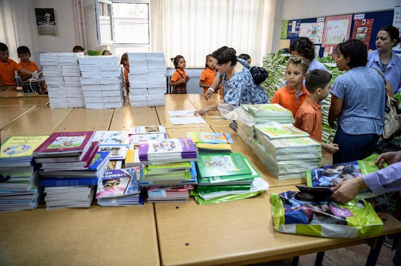 School children stand in line waiting to receive their text books on the first day back at school in Istanbul on September 19, 2016