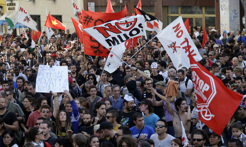Demonstrators wave flags and shout slogans during a protest in Rome, Saturday, Oct. 19, 2013. Anti-austerity protesters in Rome threw eggs and firecrackers at the Finance Ministry during a march against cuts to welfare programs and a shortage in low-income housing. More than 4,000 riot police were dispatched to maintain order as tens of thousands of protesters marched through the capital on Saturday. There were moments of tension when demonstrators passed near the headquarters of an extreme-right group, but police intervened when a few bottles were thrown. (AP Photo/Gregorio Borgia)