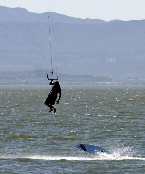 A wind surfer loses his board Monday, May 12, 2014, off Crown Memorial Beach in Alameda, Calif. After a hot, windy Mother's Day with temperatures in the mid-80s, a high pressure system was expected to heighten the heat slightly Monday before pushing it to near triple digits in some spots midweek, mostly inland areas already badly parched by drought. High temperatures will extend up and down California, according to the National Weather Service. (AP Photo/Ben Margot)