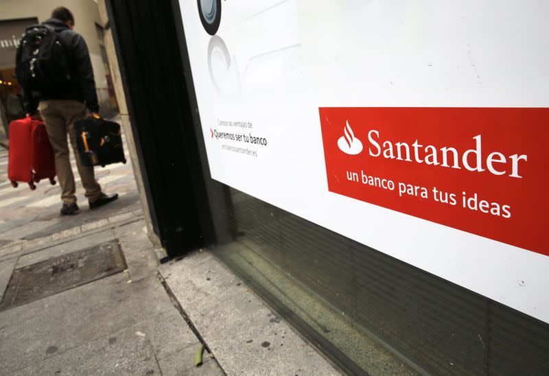 A man walks past a Santander bank branch in central Madrid
