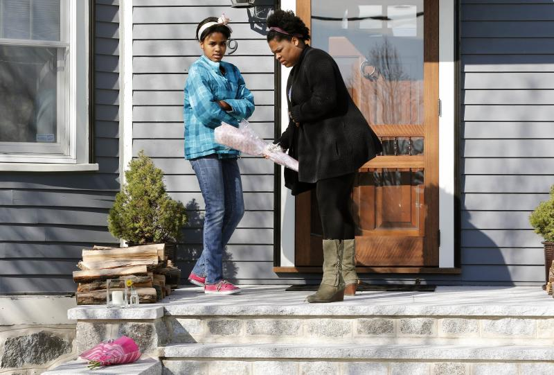 Two women place flowers on the doorstep of the Richard house in the Dorchester neighborhood of Boston, Tuesday, April 16, 2013. Martin Richard, 8, was killed in the Mondays bombings at the finish line of the Boston Marathon. The boy's mother, Denise, and 6-year-old sister, Jane, were badly injured.  (AP Photo/Michael Dwyer)