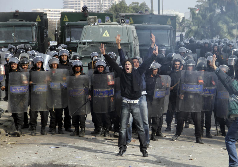 FILE - In this Friday, Jan. 28, 2011 file photo, an Egyptian protester shouts in front of anti-riot policemen who blocked a bridge in Cairo, Egypt. More Arabs are politically engaged than ever before, demanding to be heard. They're learning what it means to question everything and everyone after decades under heavy autocracies where discussion, innovation and public participation were discouraged or crushed. This week, as Egyptians prepare to mark on Friday the anniversary of the start of the revolution that swept aside Hosni Mubarak, the issue seems to come up at every panel that even tangentially touches on politics or strategy. (AP Photo/Ahmed Ali, File)