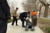 An officer helps up a drunk man passed out by a trash bin in Poksam County, in northwestern China's Xinjiang Uyghur Autonomous Region on March 21, 2021. Four years after Beijing's brutal crackdown on largely Muslim minorities native to Xinjiang, Chinese authorities are dialing back the region's high-tech police state and stepping up tourism. But even as a sense of normality returns, fear remains, hidden but pervasive. (AP Photo/Ng Han Guan)