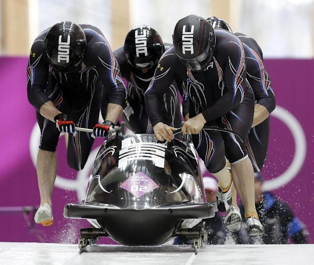 The team from the United States USA-1, with Steven Holcomb, Curtis Tomasevicz, Steven Langton and Christopher Fogt, start their third run during the men's four-man bobsled competition final at the 2014 Winter Olympics, Sunday, Feb. 23, 2014, in Krasnaya Polyana, Russia. (AP Photo/Natacha Pisarenko)