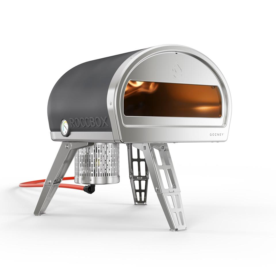 """This portable, insulated oven can cook a fresh pizza in 60 seconds. Ideal for the kind of dad who gets obsessive—he'll really be able to show off and make dozens of pizzas in less than an hour. It is capable of of burning wood or gas, and reaches temperatures over 932° F. It's quite heavy, but highly impressive. Plus, it comes in this dark gray or a bright lime green. <a href=""""https://www.gozney.com/store/us/rocc-ovens/roccbox"""" rel=""""nofollow"""">SHOP NOW</a>: Roccbox Portable Pizza Oven by Gozney, $599, gozney.com"""