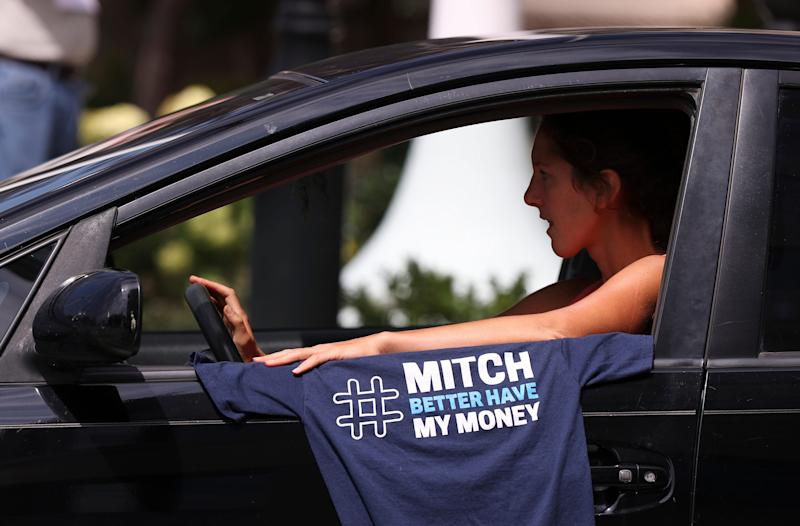 A car caravan drove past the federal courthouse to demand that Sen. Mitch McConnell reinstate unemployment benefits.