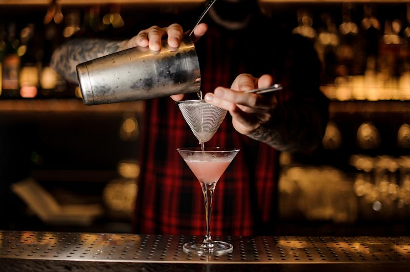 Barman pouring fresh and tasty Cosmopolitan cocktail into an elegant martini glass using shaker and strainer