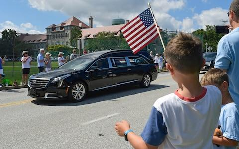 People watch as the casket of John McCain is taken to the US Naval Academy - Credit: Susan Walsh/AP