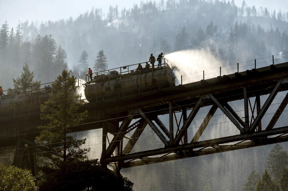 Firefighters spray water from Union Pacific Railroad's fire train while battling the Dixie Fire in Plumas National Forest, Calif., on Friday, July 16, 2021. (AP Photo/Noah Berger)