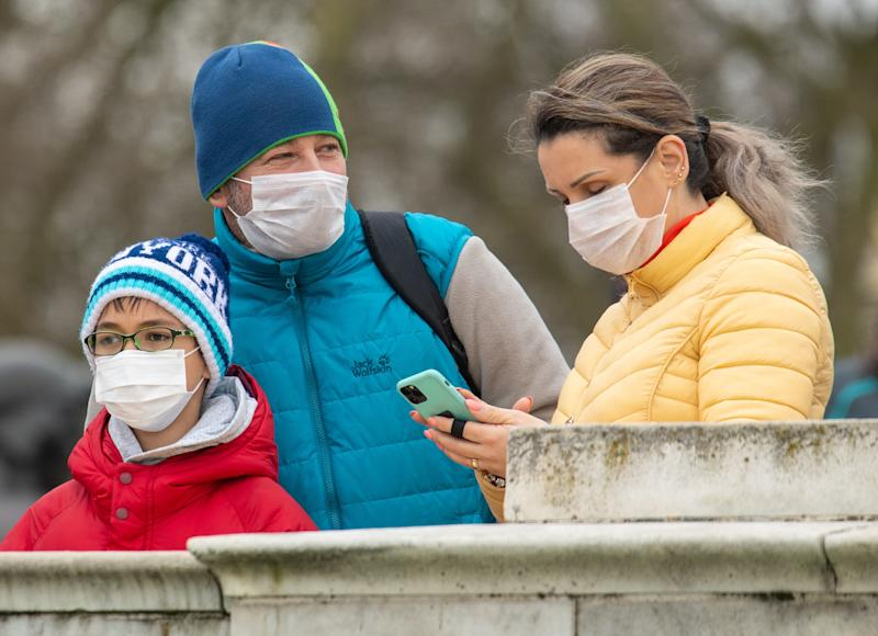 "People wearing protective face masks watch the Changing of the Guard ceremony outside Buckingham Palace, London, the day after the Prime Minister said that Covid-19 ""is the worst public health crisis for a generation"", and the government's top scientist warned that up to 10,000 people in the UK are already infected. PA Photo. Picture date: Friday March 13, 2020. See PA story HEALTH Coronavirus. Photo credit should read: Dominic Lipinski/PA Wire (Photo by Dominic Lipinski/PA Images via Getty Images)"