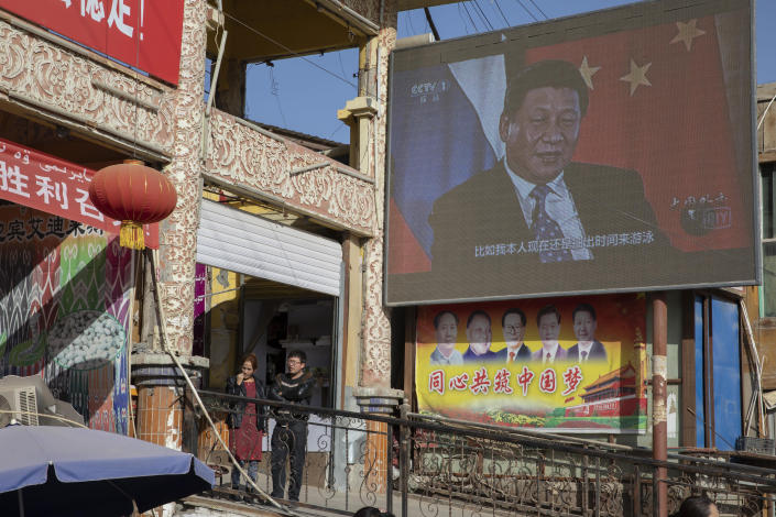 Chinese President Xi Jinping is seen on a screen near a bazaar in Hotan in western China's Xinjiang region, China, Friday, Nov. 3, 2017. The accusation of genocide by U.S. Secretary of State Mike Pompeo against China touches on a hot-button human rights issue between China and the West. (AP Photo/Ng Han Guan)