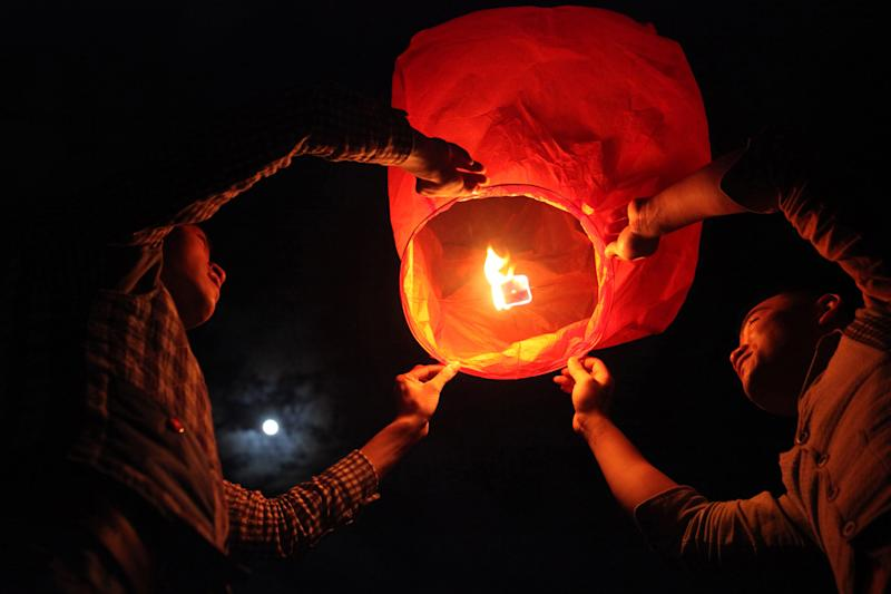 File photo taken in October 2012 shows a coulpe lighting a lantern for the Mid-Autumn Festival before their same-sex wedding ceremony in China's Fujian province