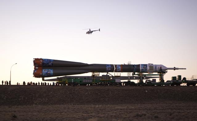 A police helicopter flies above the Soyuz TMA-11M spacecraft decorated with 2014 Sochi Winter Olympic Games' patterns, as it is transported to its launch pad at the Baikonur cosmodrome November 5, 2013. The Soyuz spacecraft will carry Japanese astronaut Koichi Wakata, Russian cosmonaut Mikhail Tyurin and U.S. astronaut Rick Mastracchio to the International Space Station (ISS) on November 7. REUTERS/Shamil Zhumatov (KAZAKHSTAN - Tags: SCIENCE TECHNOLOGY SOCIETY SPORT OLYMPICS)