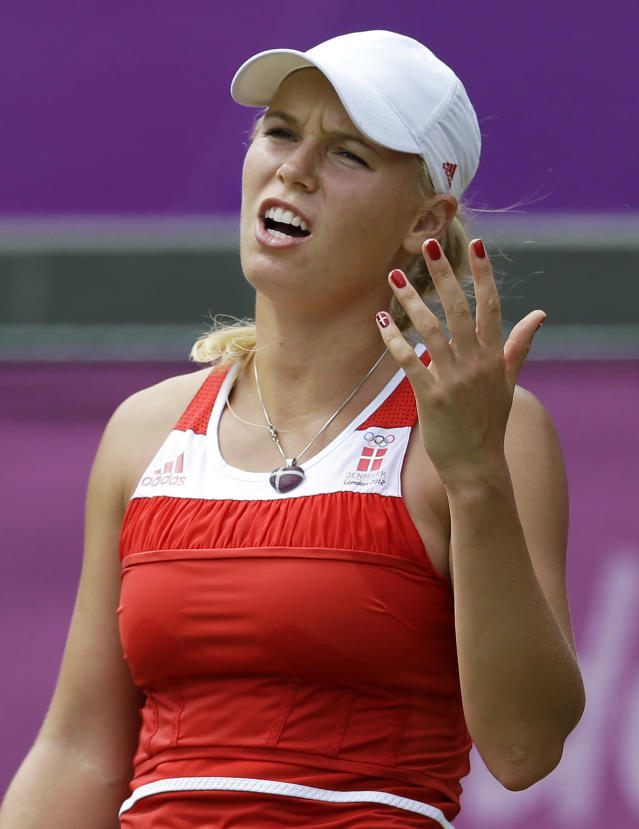 Caroline Wozniacki of Denmark reacts to losing a point to Serena Williams of the United States at the All England Lawn Tennis Club at Wimbledon, in London, at the 2012 Summer Olympics, Thursday, Aug. 2, 2012. (AP Photo/Mark Humphrey)