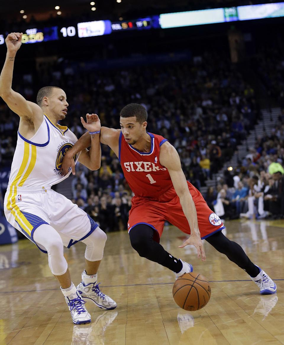 Philadelphia 76ers' Michael Carter-Williams (1) dribbles next to Golden State Warriors' Stephen Curry during the first half of an NBA basketball game, Monday, Feb. 10, 2014, in Oakland, Calif. (AP Photo/Marcio Jose Sanchez)