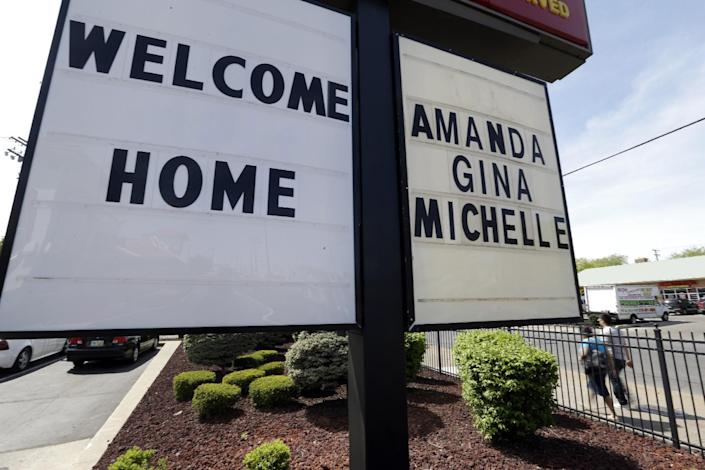"FILE - In this Thursday, May 9, 2013 file photo, a ""Welcome Home"" sign is posted at a restaurant near a crime scene where three women were held captive for a decade in Cleveland. For Gina DeJesus, Amanda Berry and Michelle Knight, who were freed from captivity inside a Cleveland house Monday, May 6, 2013, the ordeal is not over. Next comes recovery _ from sexual abuse and their sudden, jarring reentry into a world much different than the one they were snatched from a decade ago. (AP Photo/David Duprey, File)"