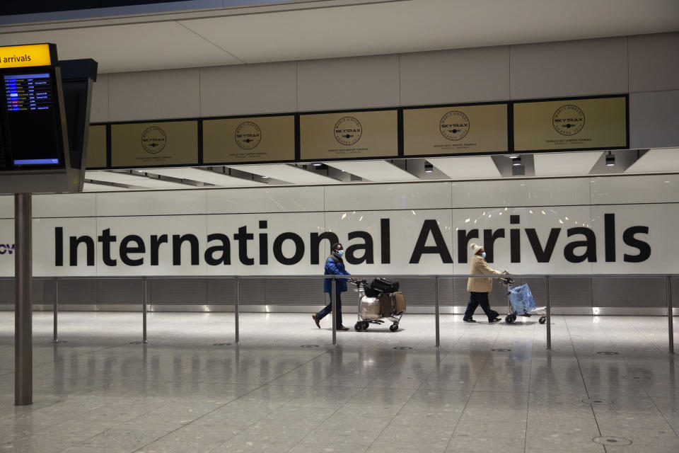 """FILE - In this Tuesday, Jan. 26, 2021 file photo, arriving passengers walk past a sign in the arrivals area at Heathrow Airport in London. A terminal at Heathrow Airport mothballed because of the coronavirus pandemic has reopened Tuesday, June 1 for passengers arriving from high-risk countries. Britain has barred travelers from a """"red list"""" of 43 coronavirus hotspots including India, Brazil, Turkey and South Africa. U.K. nationals and residents who return from those countries face a mandatory 10-day supervised quarantine in a hotel.(AP Photo/Matt Dunham, File)"""