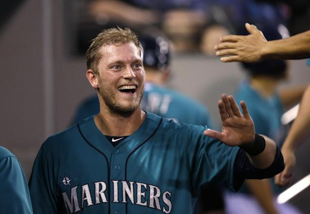 Seattle Mariners' Michael Saunders smiles as he is congratulated in the dugout on his home run against the Minnesota Twins in the seventh inning of a baseball game Monday, July 7, 2014, in Seattle. (AP Photo/Elaine Thompson)