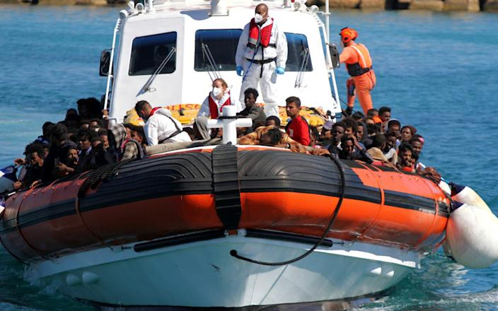 Migrants aboard a search-and-rescue boat approaching the island of Lampedusa - Reuters