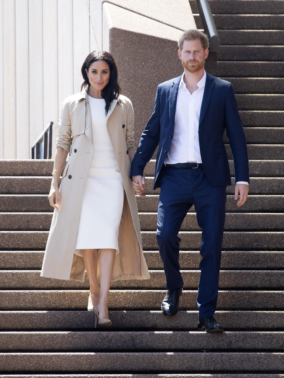 Markle topped a white dress with a beige trench coat when she and Prince Harry arrived in Australia one day after Markle's pregnancy was announced. (Photo: Getty Images)