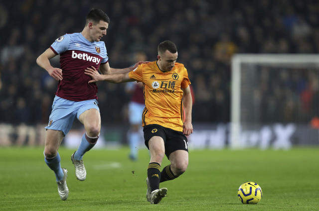 West Ham United's Declan Rice, left, and Wolverhampton Wanderers's Diogo Jota battle for the ball during their English Premier League soccer match at Molineux in Wolverhampton, England, Wednesday Dec. 4, 2019. (David Davies/PA via AP)