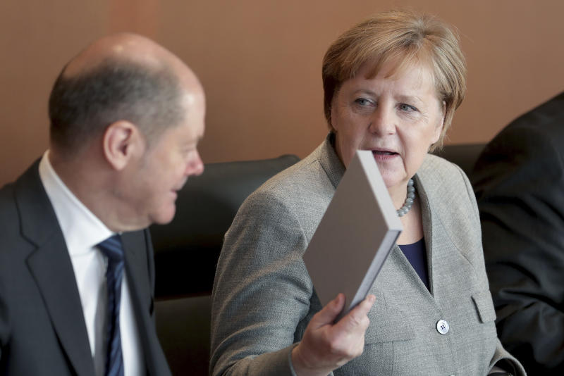 German Chancellor Angela Merkel holds a box with stamps as she arrives for the weekly cabinet meeting at the Chancellery in Berlin, Germany, Wednesday, Dec. 18, 2019. At left is German Finance Minister Olaf Scholz. (AP Photo/Michael Sohn)