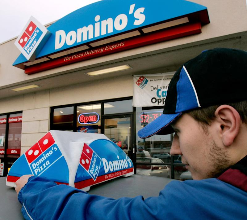 """FILE - In this Feb. 21, 2007 file photo, Domino's Pizza delivery person Brandon Christensen plugs in the company sign atop his car in Sandy, Utah. The pizza delivery chain on Monday, June 16, 2014 plans to introduce a function on its mobile app that lets customers place orders by speaking with a computer-generated voice named """"Dom."""" (AP Photo/Douglas C. Pizac, File)"""