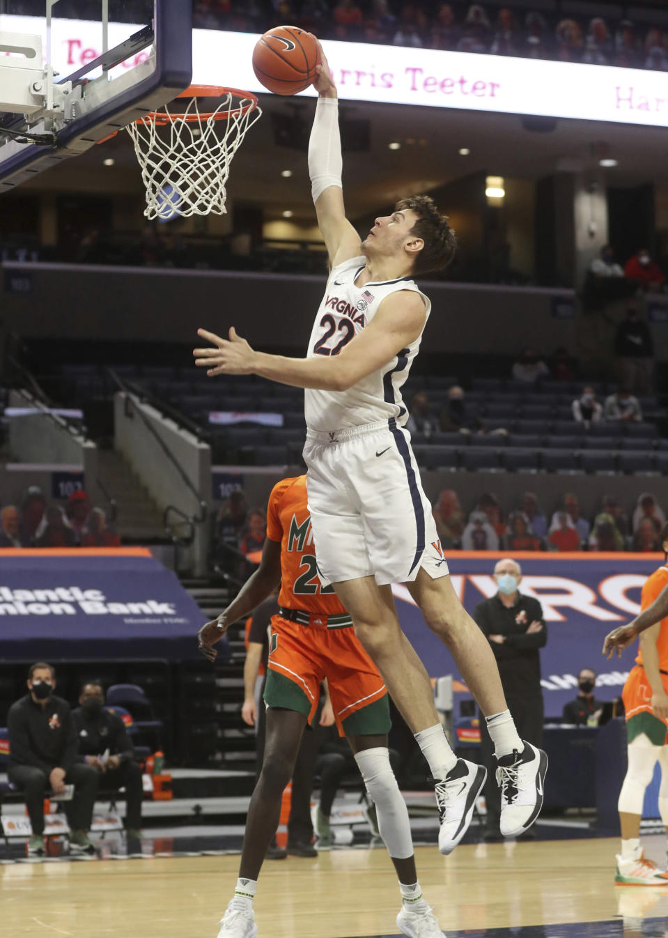 Virginia center Francisco Caffaro (22) dunks next to Miami guard Kameron McGusty (23) during an NCAA college basketball game Monday in Charlottesville, Va. (Andrew Shurtleff/The Daily Progress via AP, Pool)